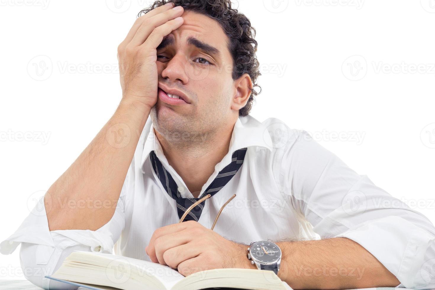 homem cansado na camisa branca, sentado com o livro foto