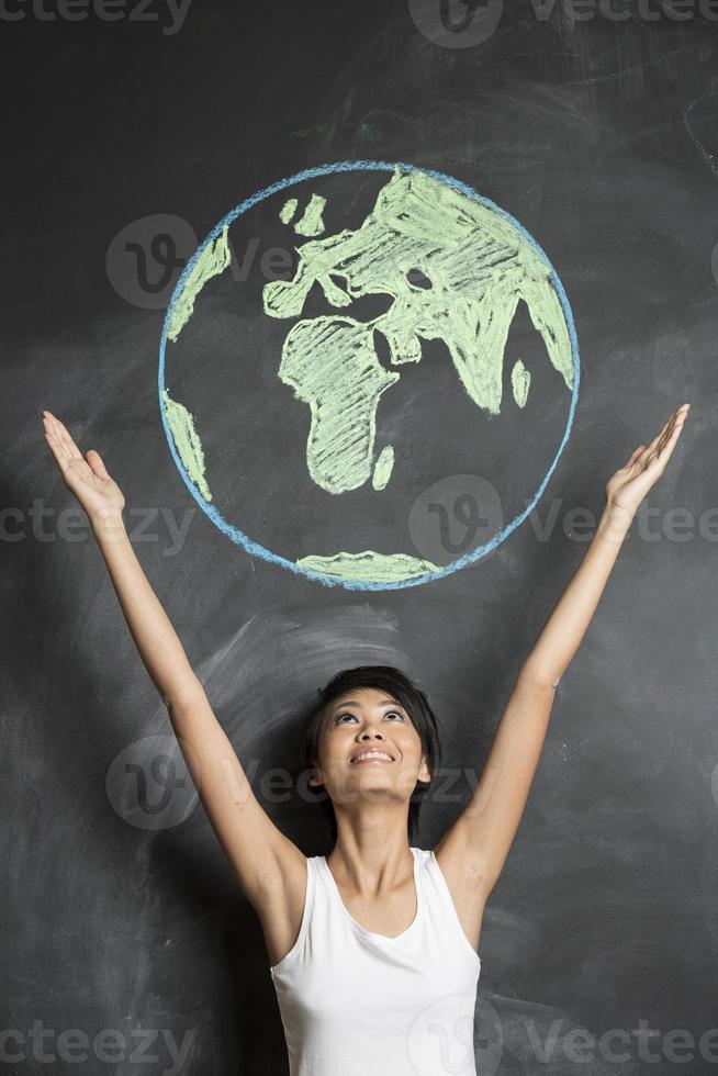 mulher atingindo os braços em direção a um desenho de terra de lousa foto