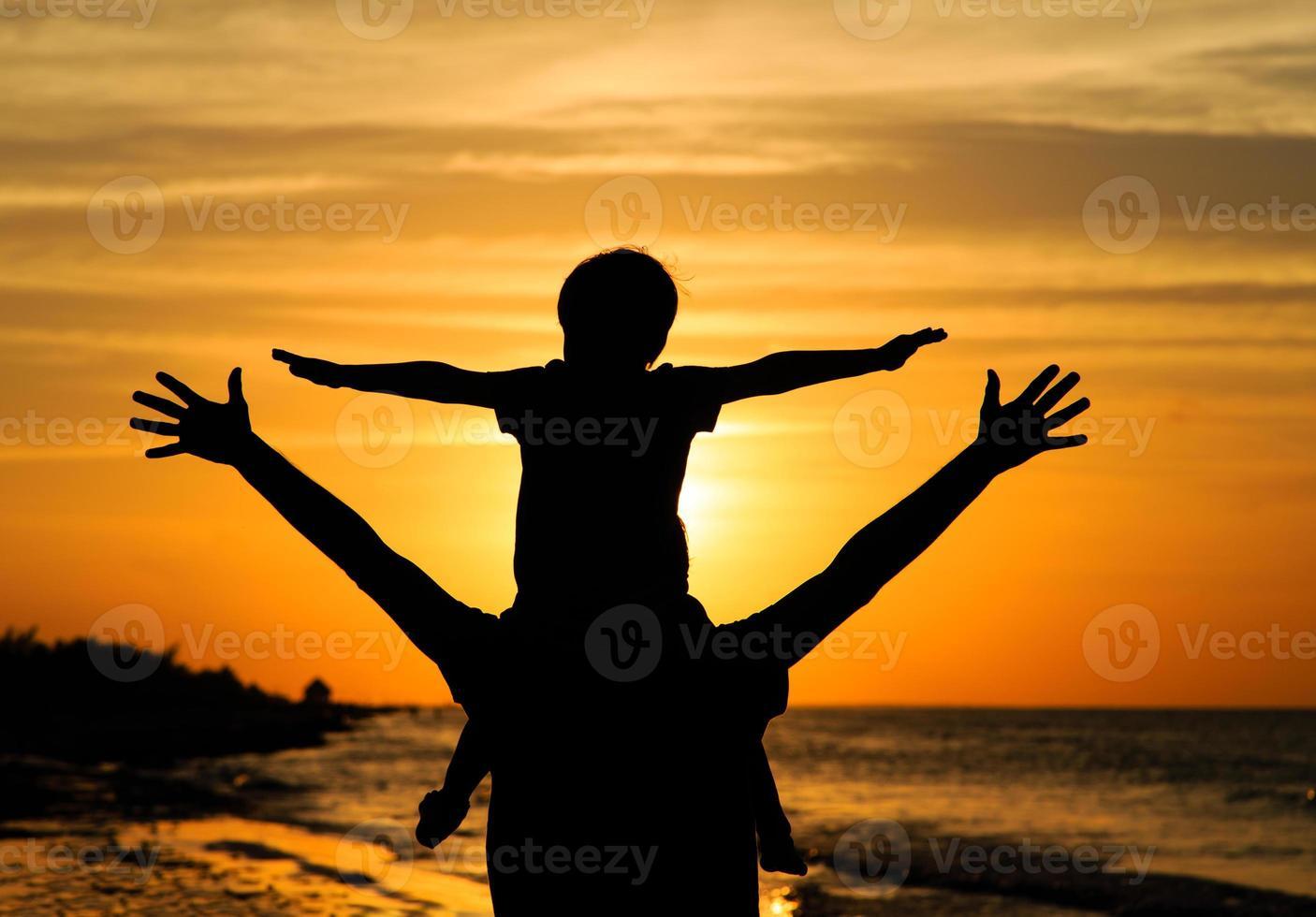 pai e filho se divertindo no pôr do sol foto