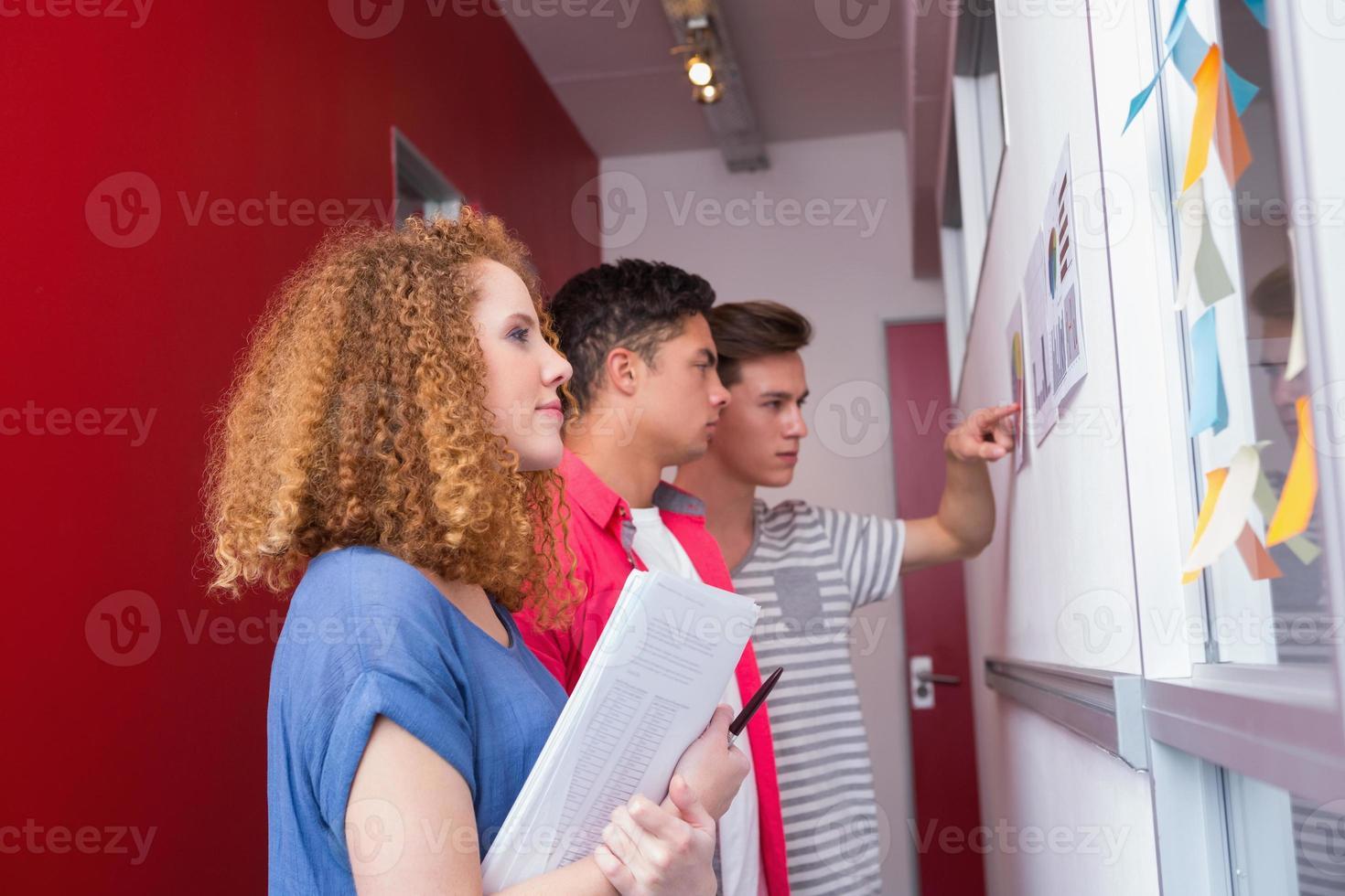 estudantes sérios estudando com gráficos na parede foto