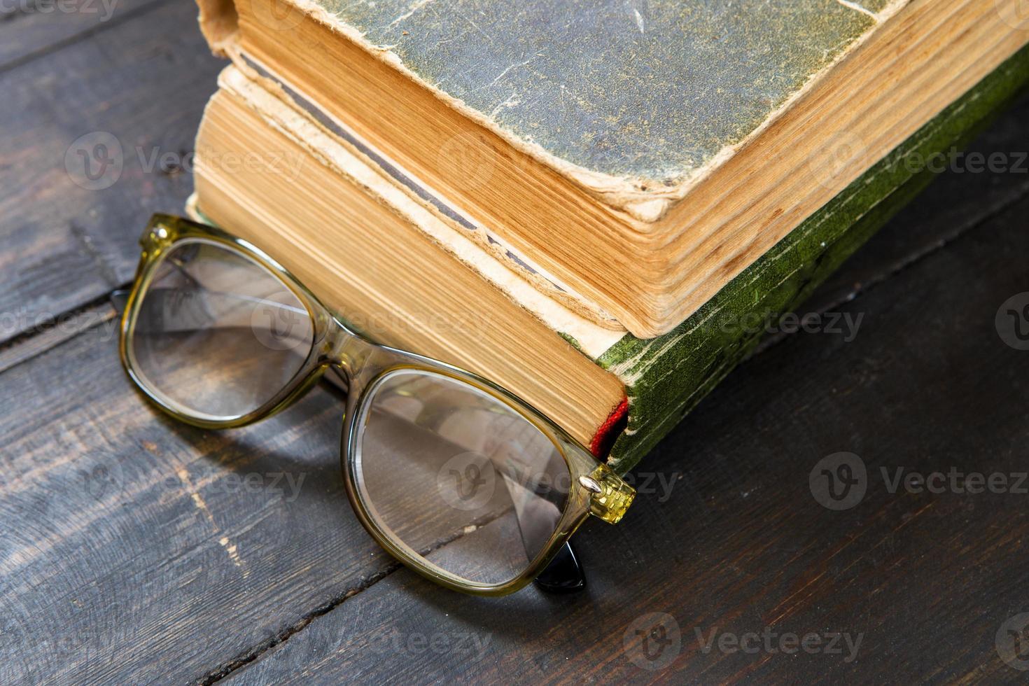 óculos de leitura vintage e o livro sobre fundo de madeira foto