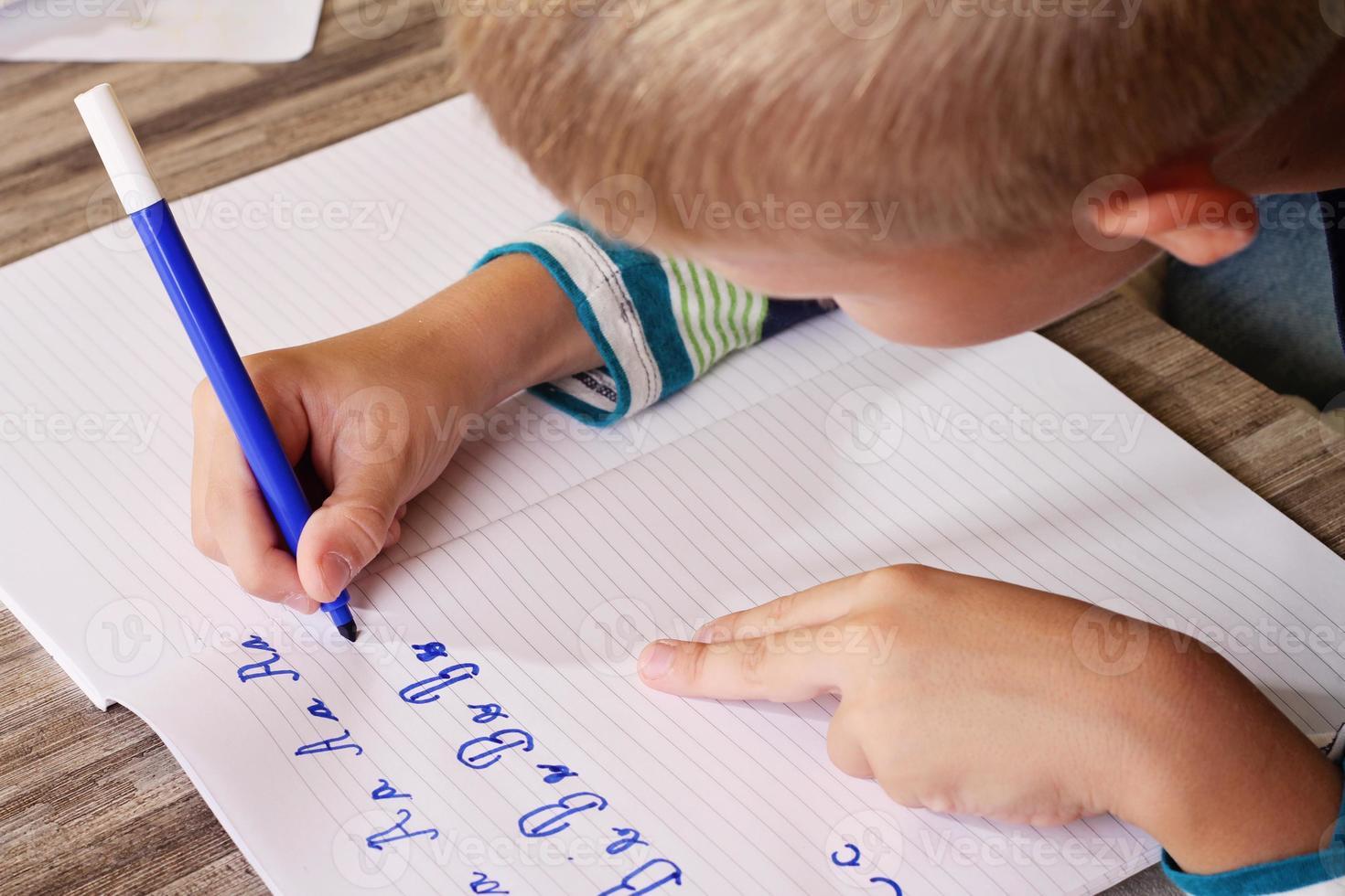 menino de escola, escrevendo no papel, escrevendo o alfabeto foto