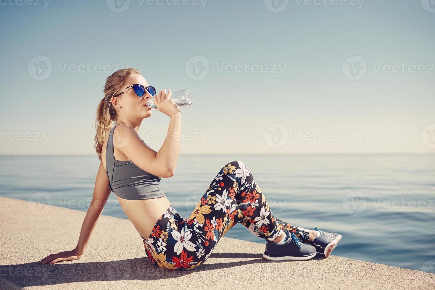 aptidão jovem mulher loira água potável depois de correr na praia. foto