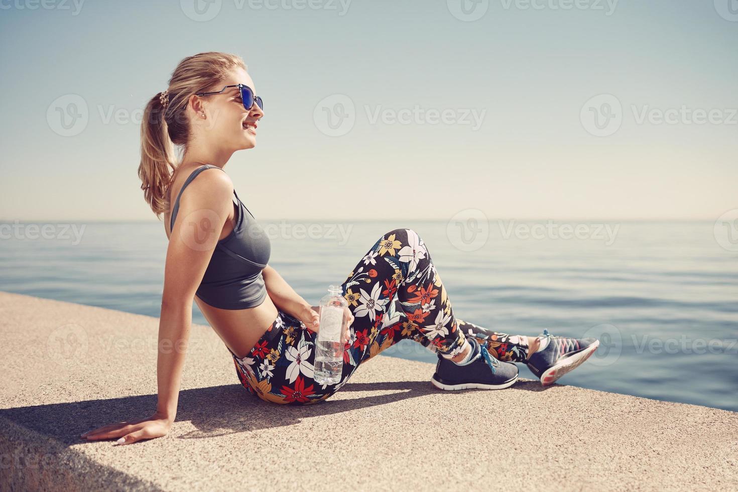 mulher loira fitness jovem segurar a garrafa após o ajuste na praia foto