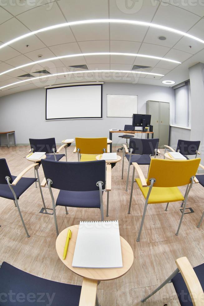 sala de aula vazia com cabelos e blocos de notas foto