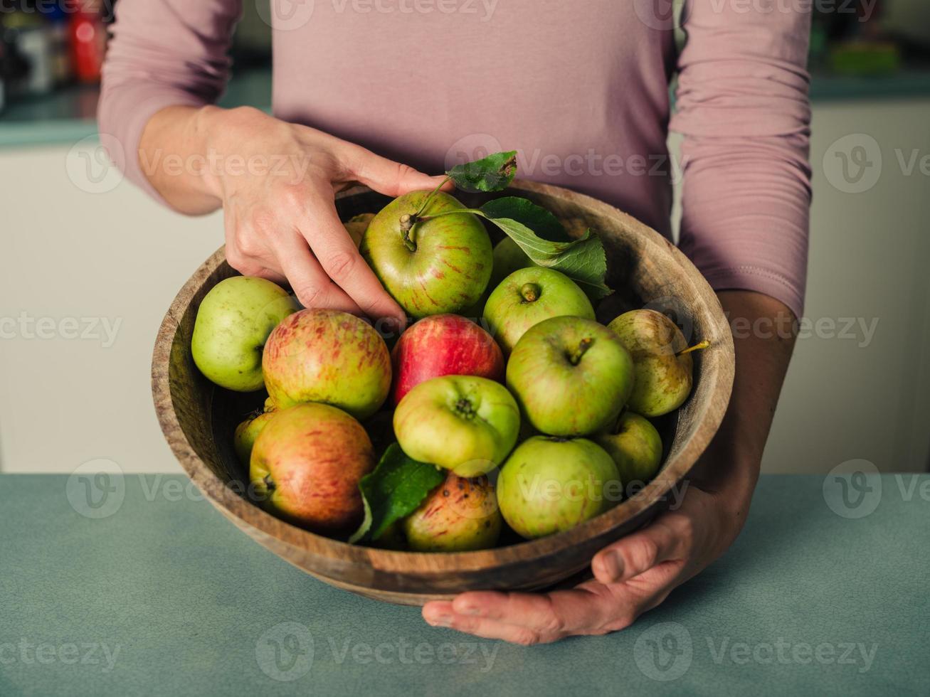 jovem mulher na cozinha com uma tigela de maçãs foto