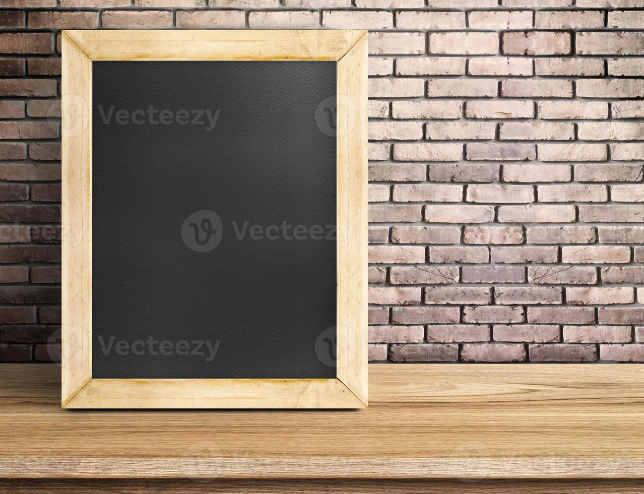 lousa em branco na mesa de madeira na parede de tijolo vermelho foto