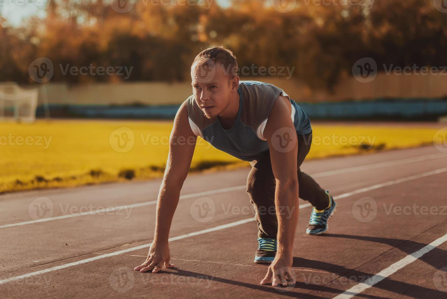homem de pé na postura pronta para correr na esteira. foto