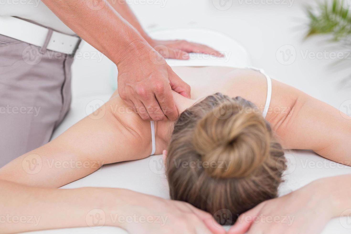 fisioterapeuta fazendo massagem nos ombros foto