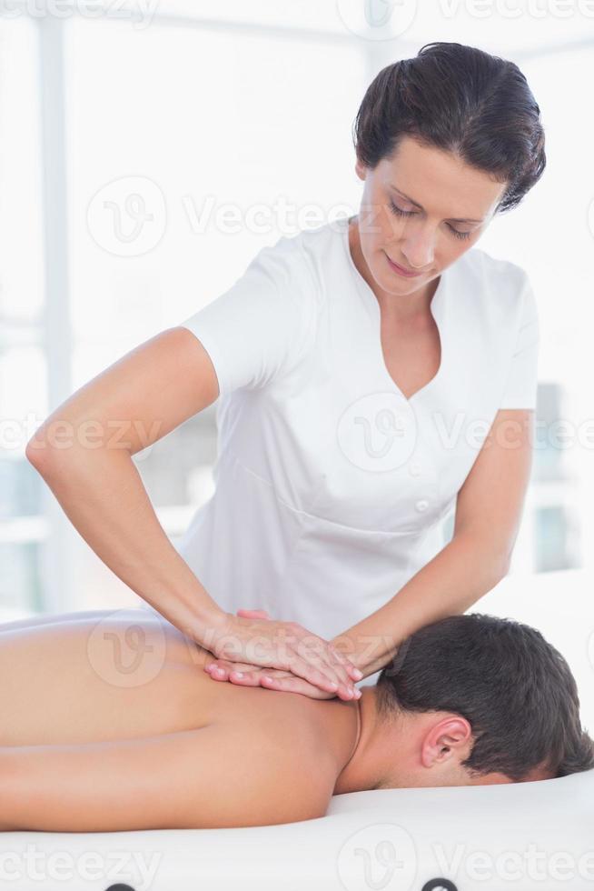 fisioterapeuta fazendo massagem nas costas para seu paciente foto