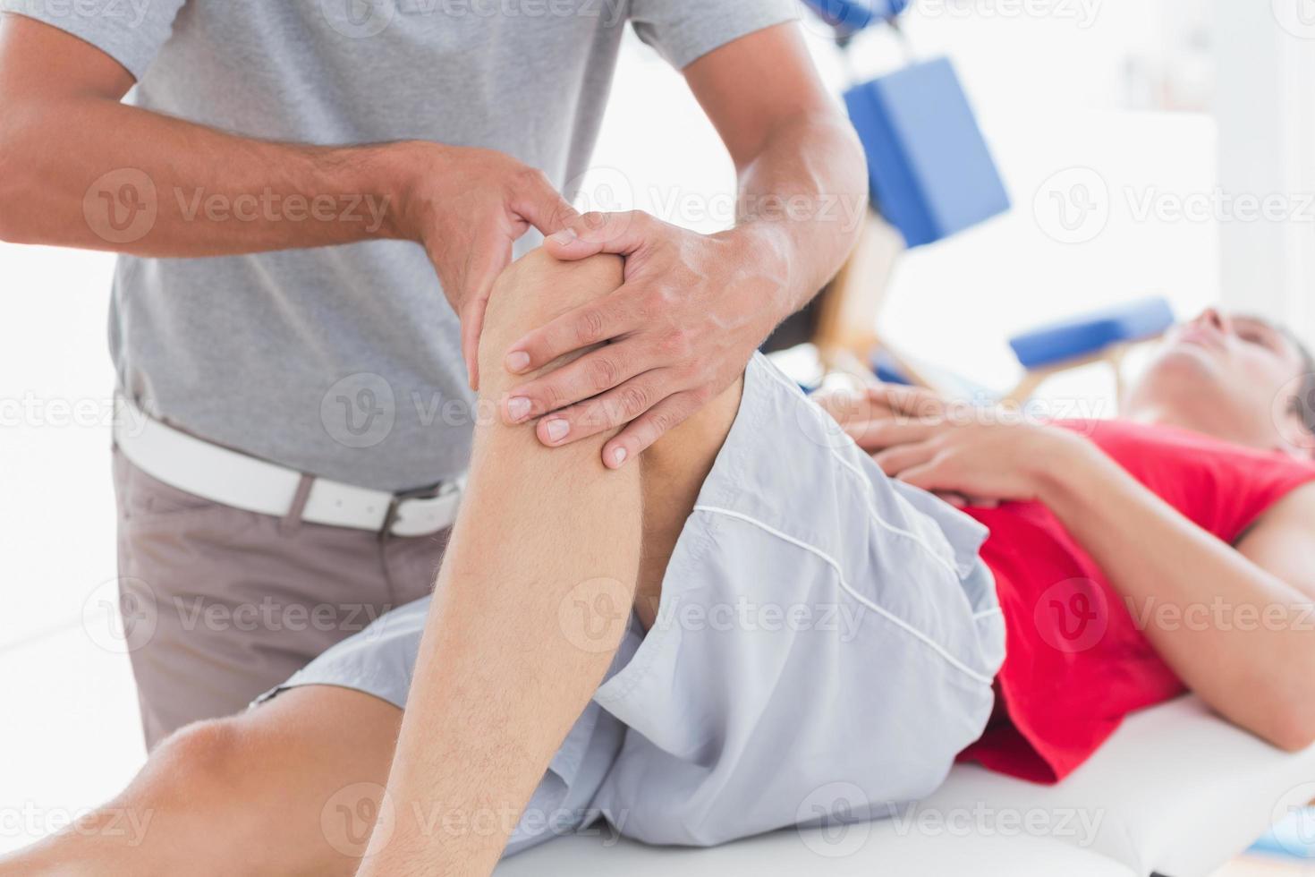 homem tendo massagem no joelho foto