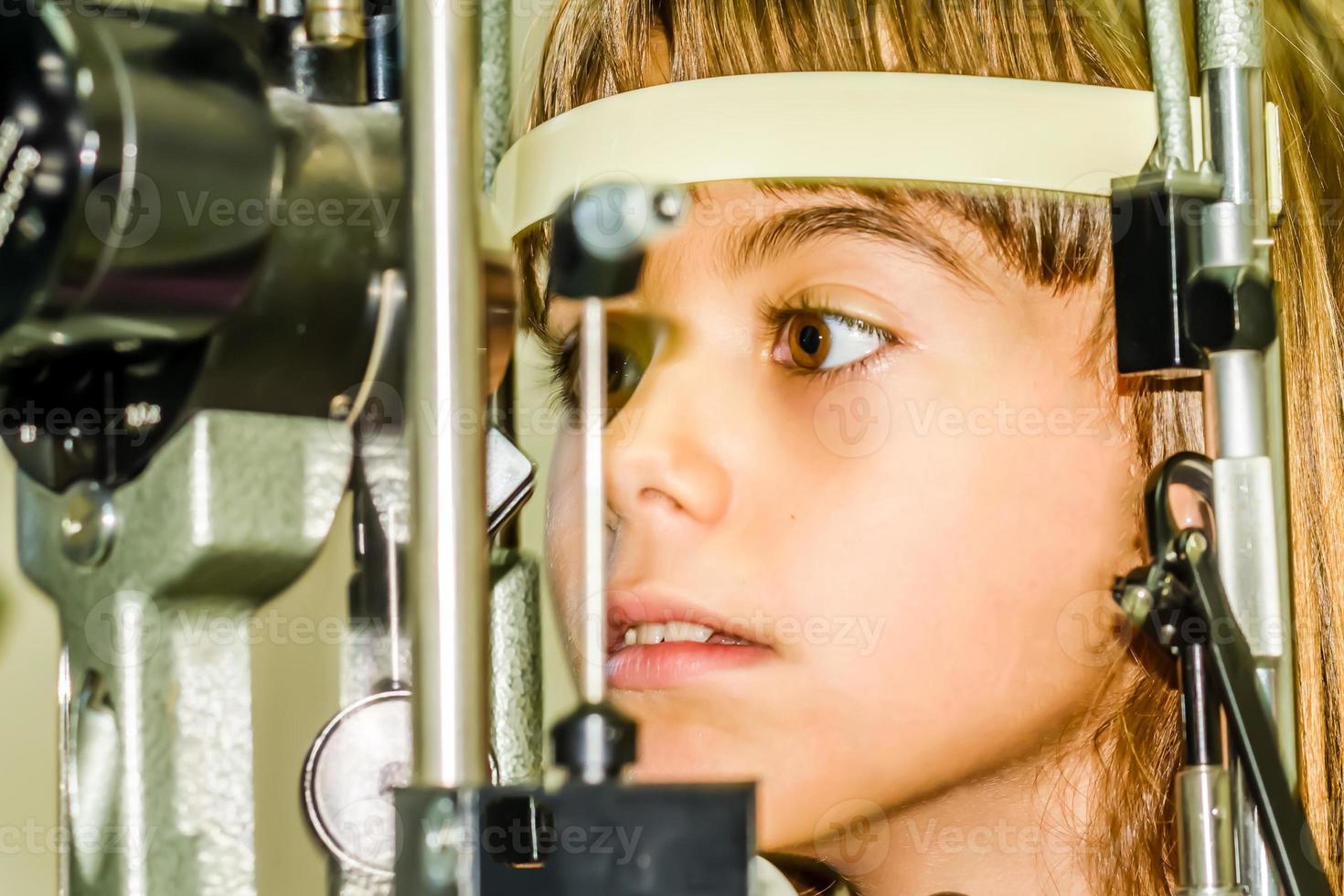litlle garota fazendo o exame oftalmológico foto