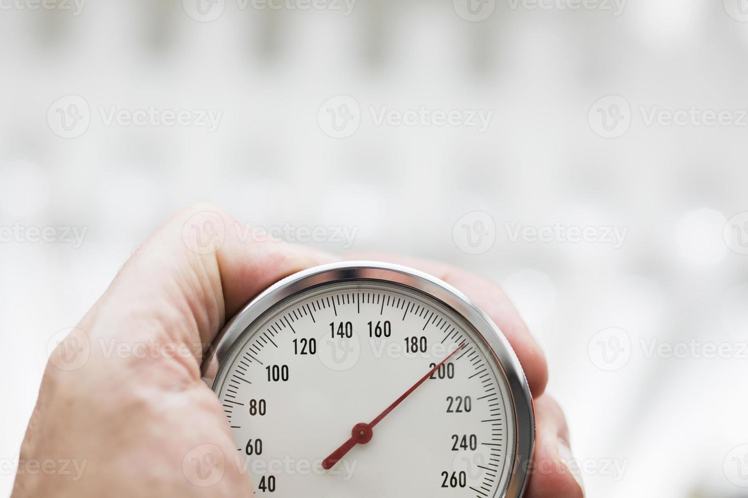 mão segurando o esfigmomanômetro close-up foto