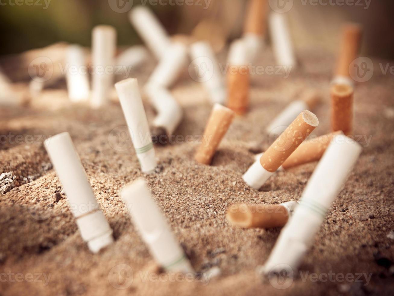 muitos cigarros queimados no cinzeiro e areia foto