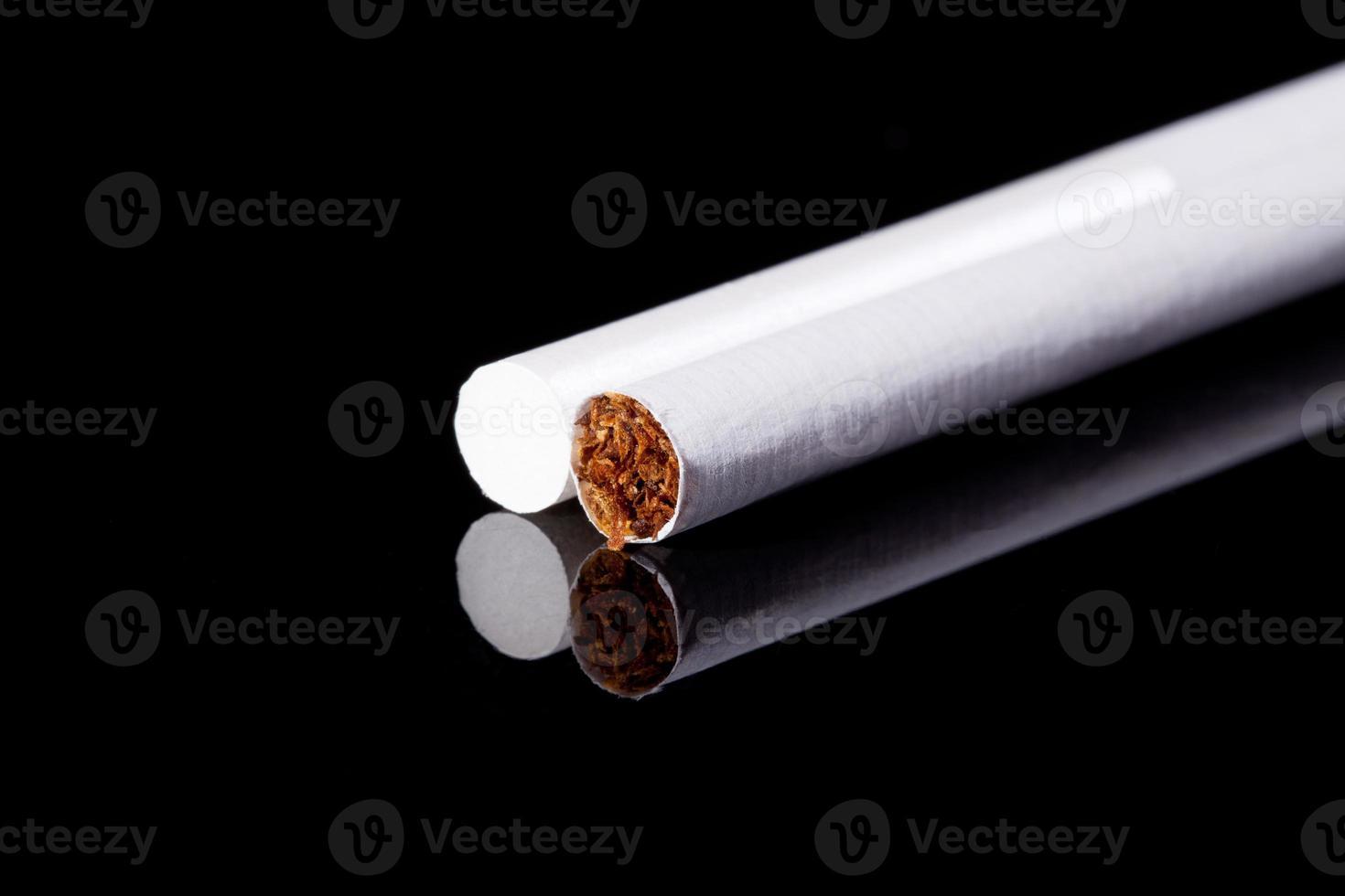 dois cigarros finos isolados na macro de fundo preto foto