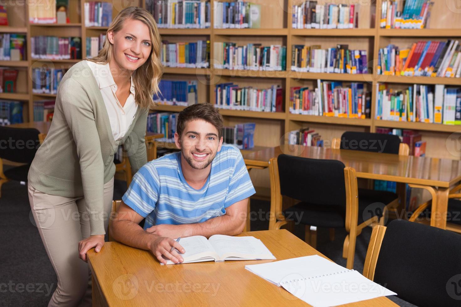 aluno recebendo ajuda do tutor na biblioteca foto