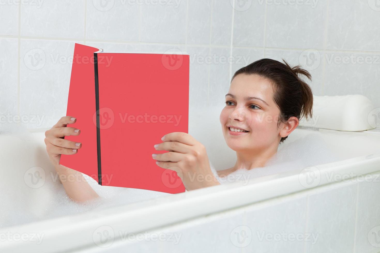 jovem mulher na banheira lendo livro foto