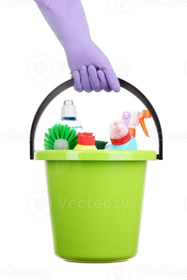 balde com itens de limpeza na mão isolado no branco foto