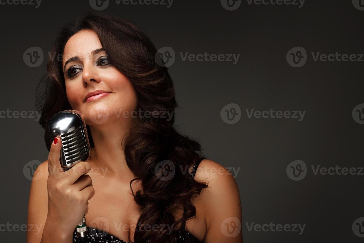 jovem cantora com microfone vintage foto