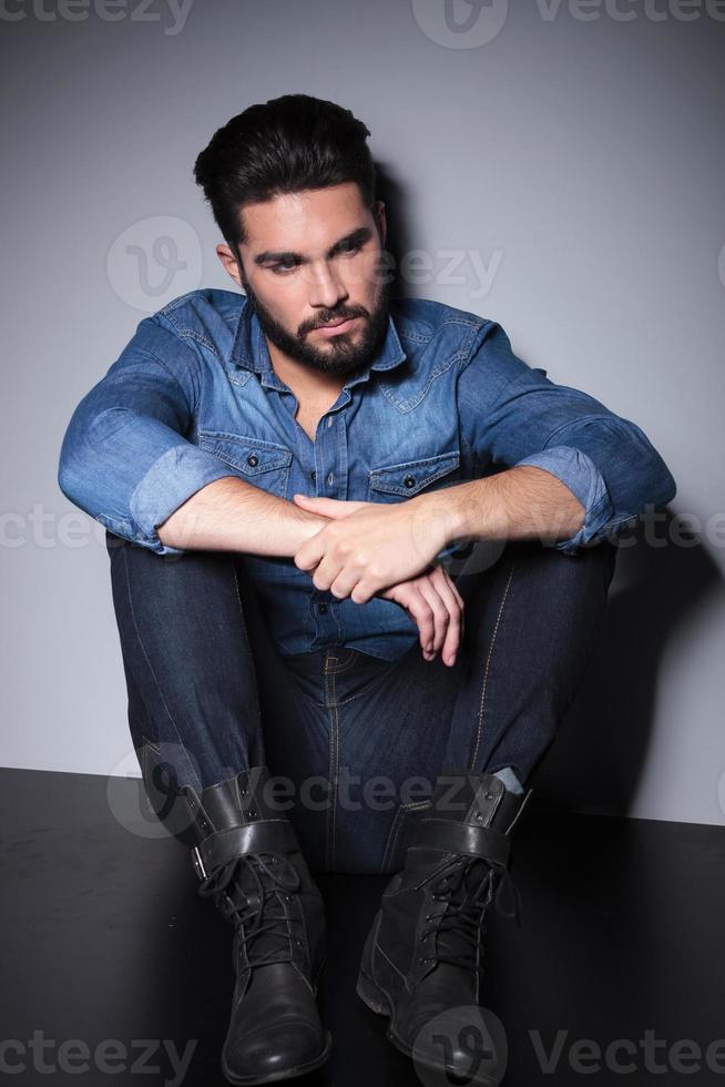 homem de camisa azul sentado foto