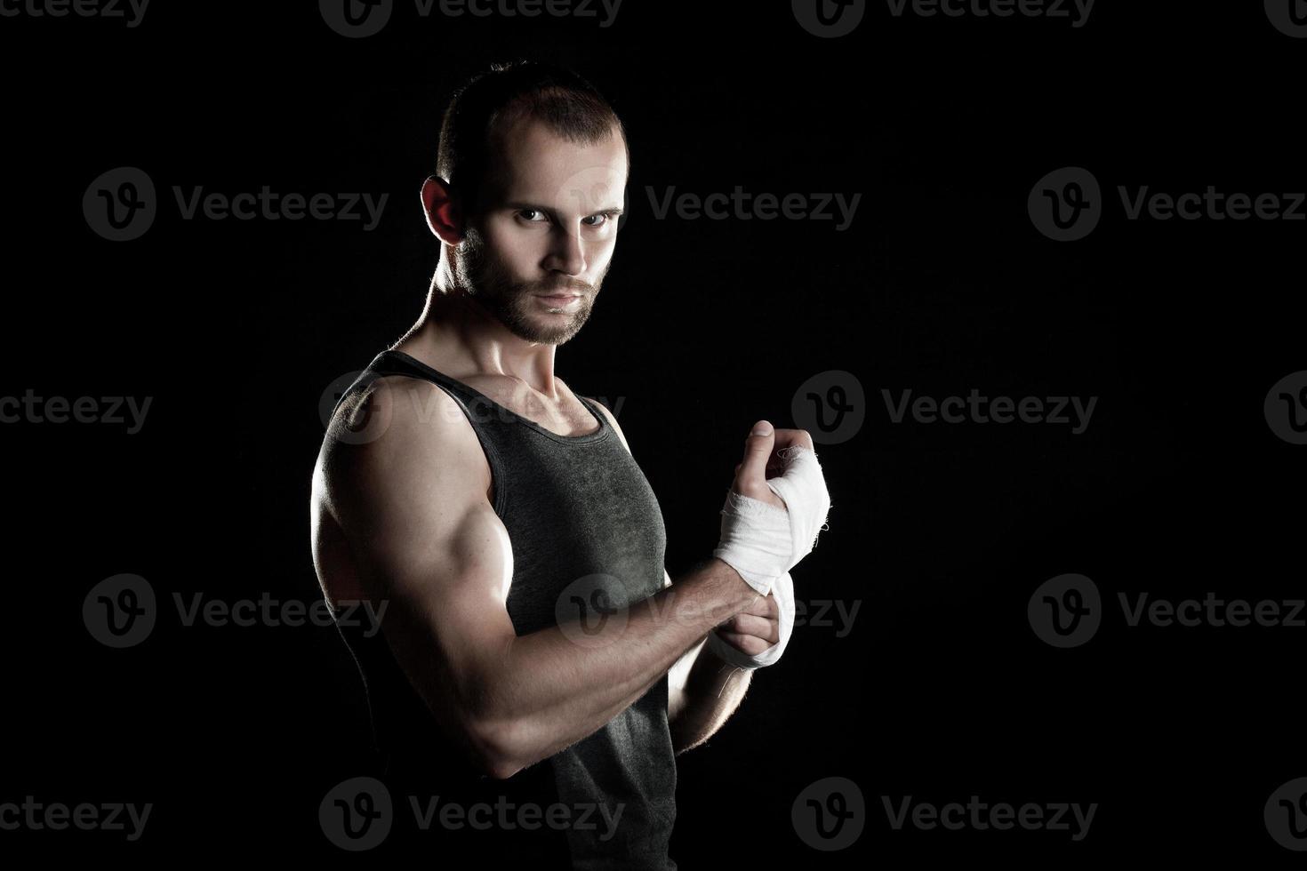 homem musculoso, amarrando um curativo elástico na mão, preto foto