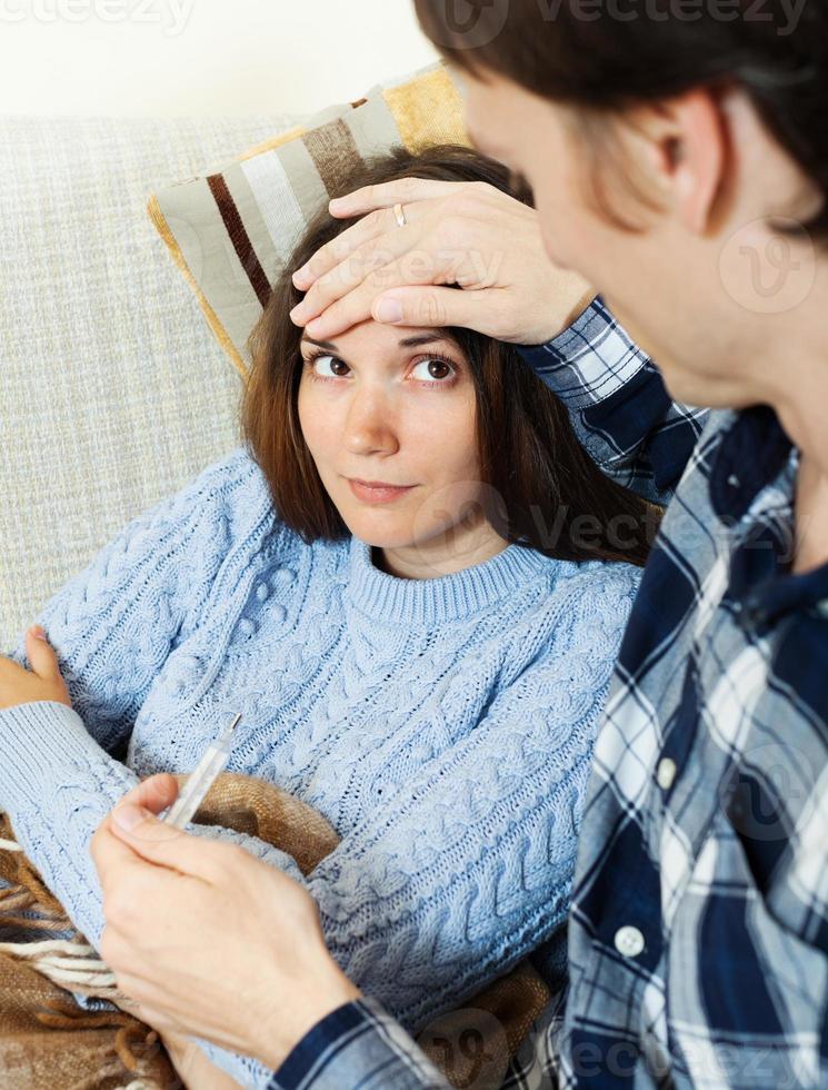 homem cuidando da namorada que tem alta temperatura foto