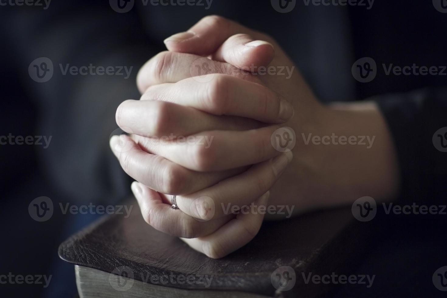 dobrar as mãos sobre uma Bíblia foto