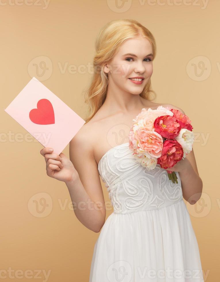 jovem mulher segurando flor e cartão postal foto