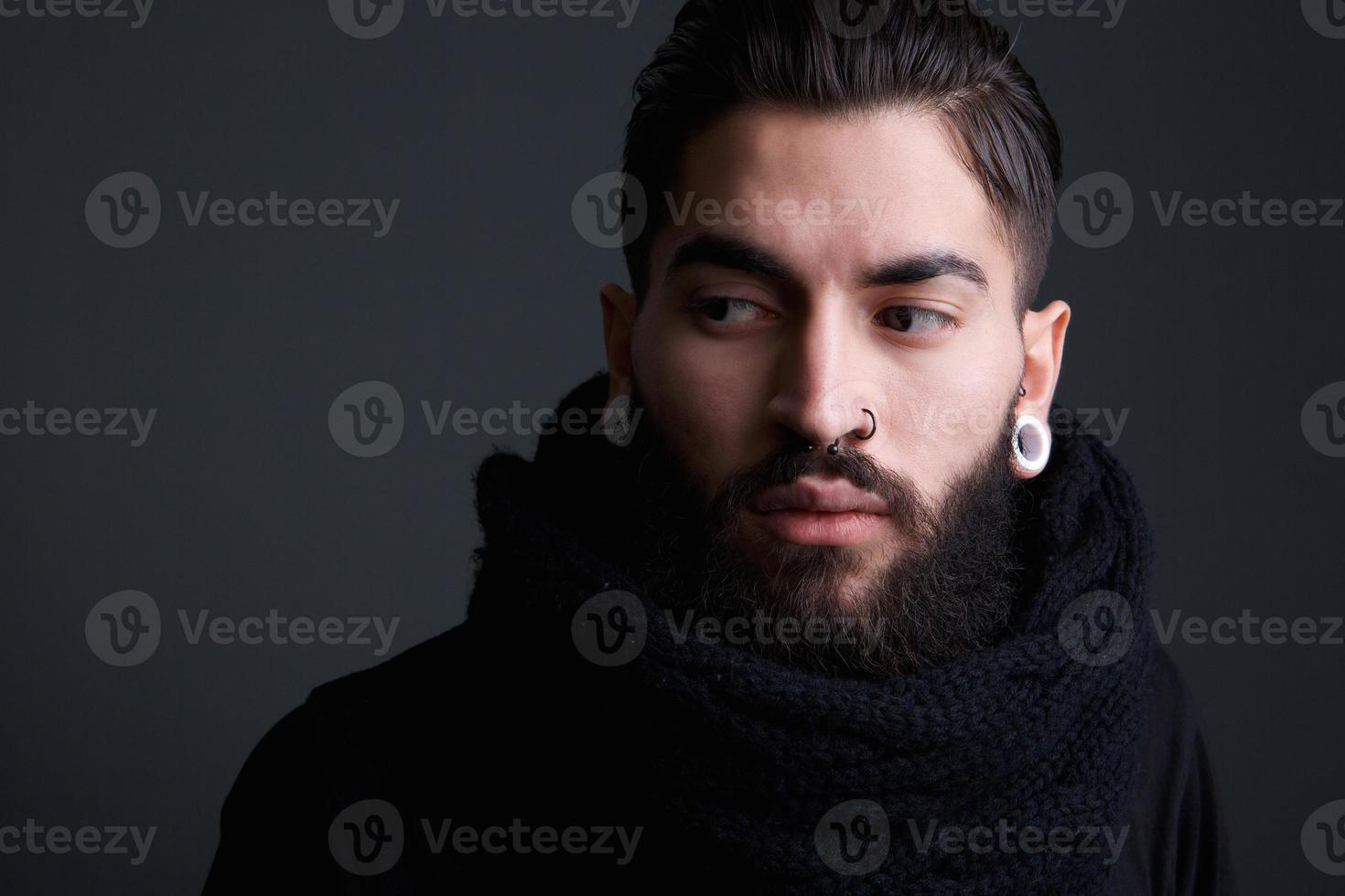 jovem moderno com barba e piercings foto