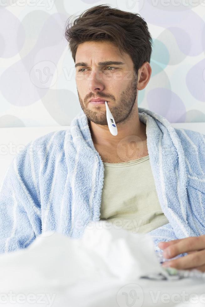 homem doente com termômetro na boca, sentada na cama foto