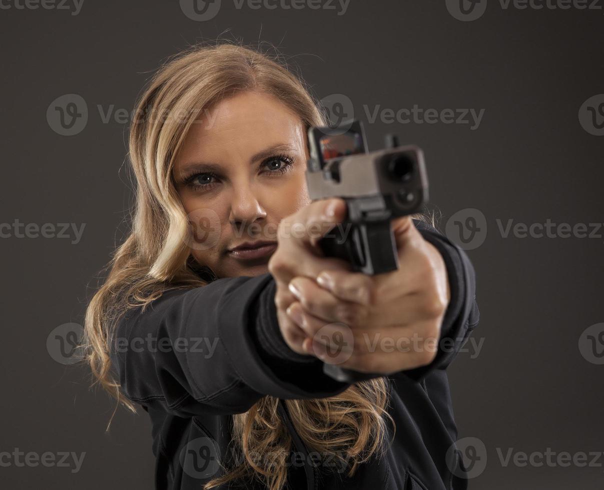 foco no atirador de mulher apontando a arma. foto
