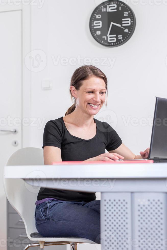 foto de mulher sorridente, trabalhando no escritório