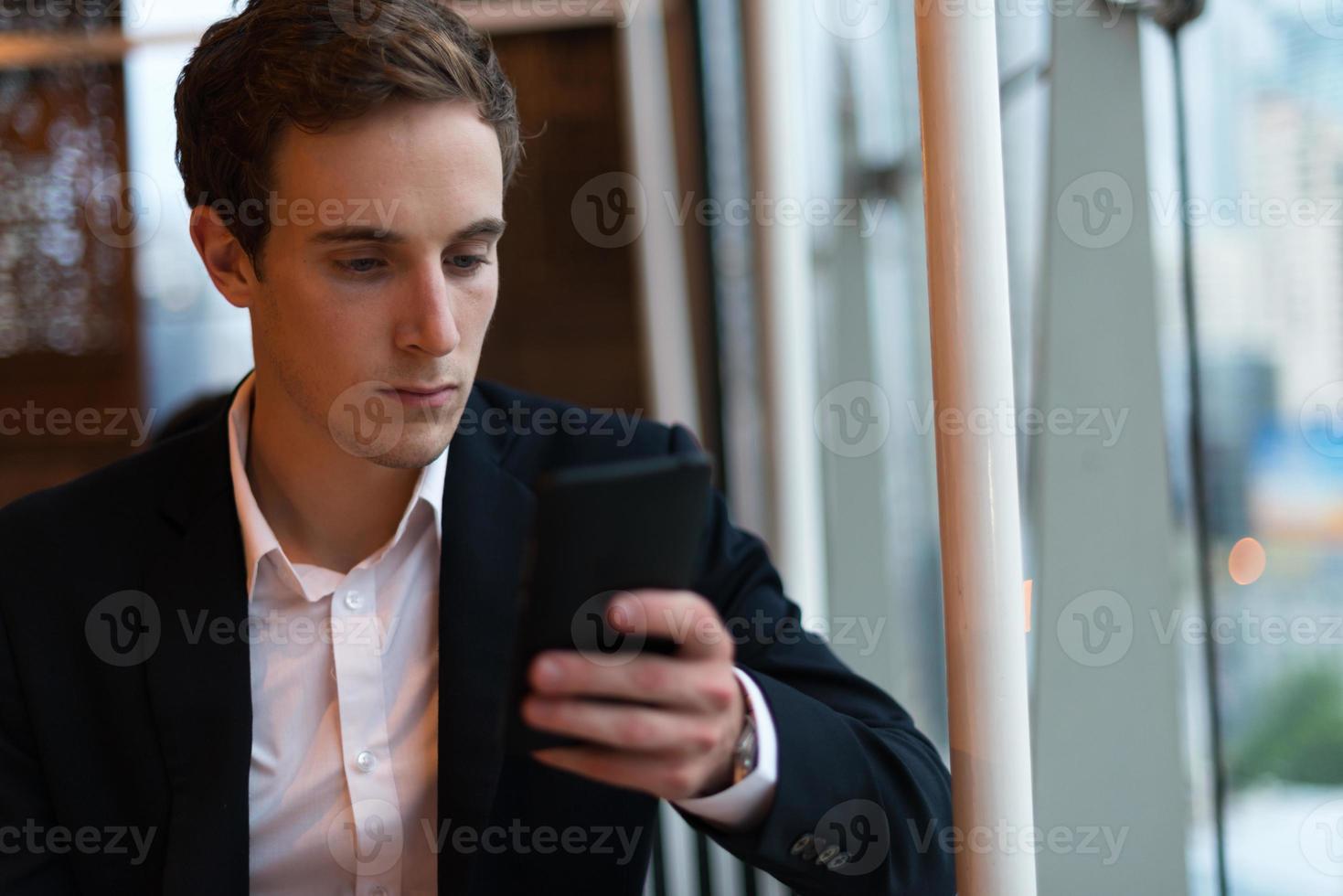 empresário, olhando para o telefone foto