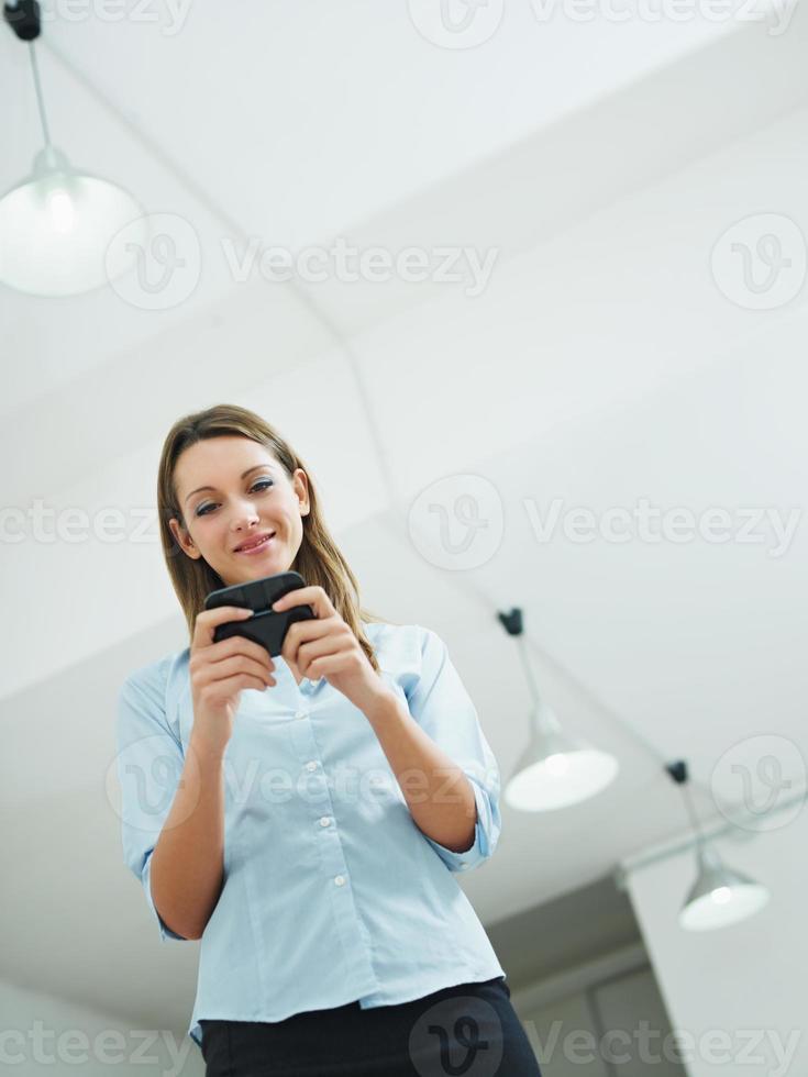 mulher lendo e-mails no celular no escritório foto