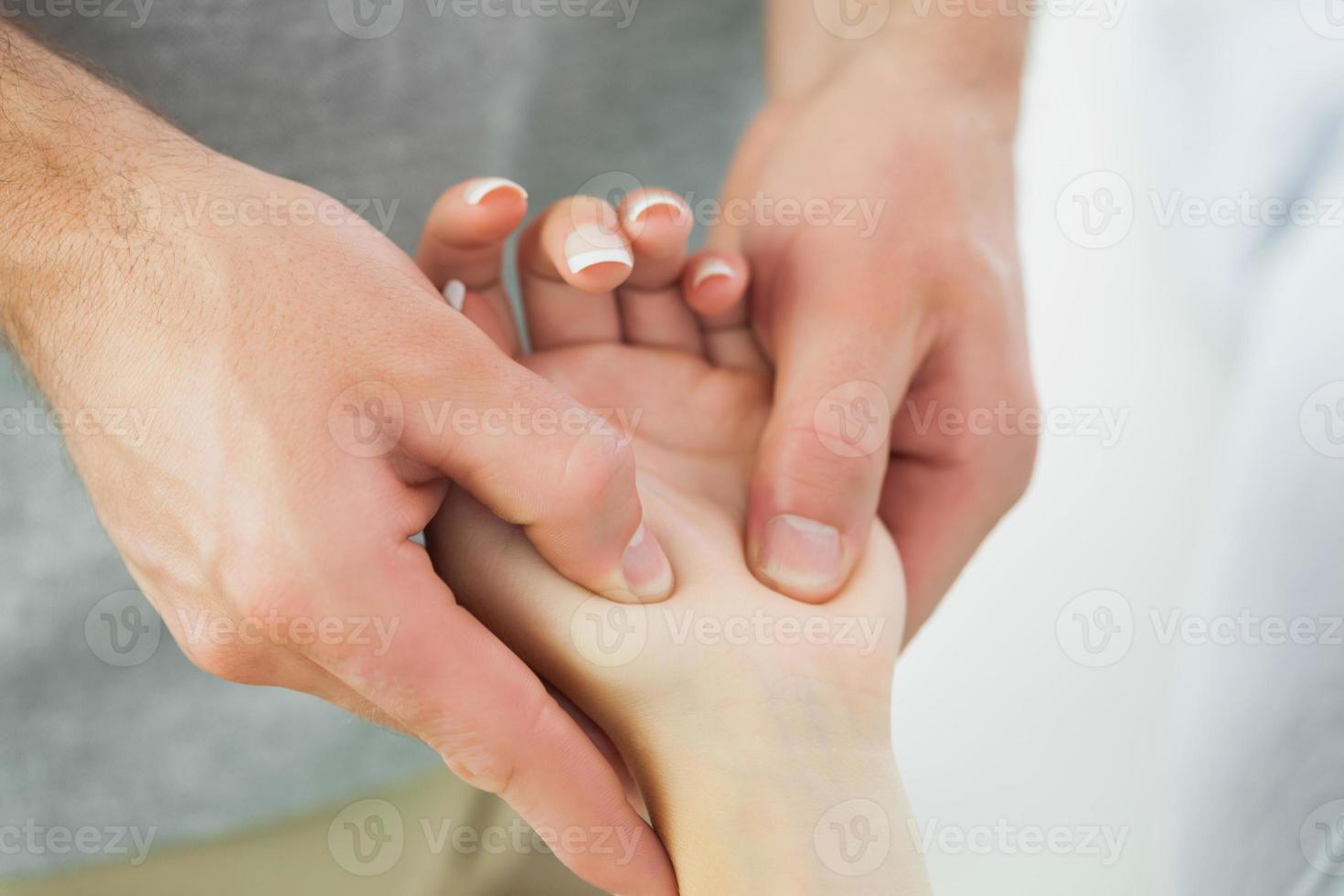 close-up de fisioterapeuta massageando pacientes mão foto