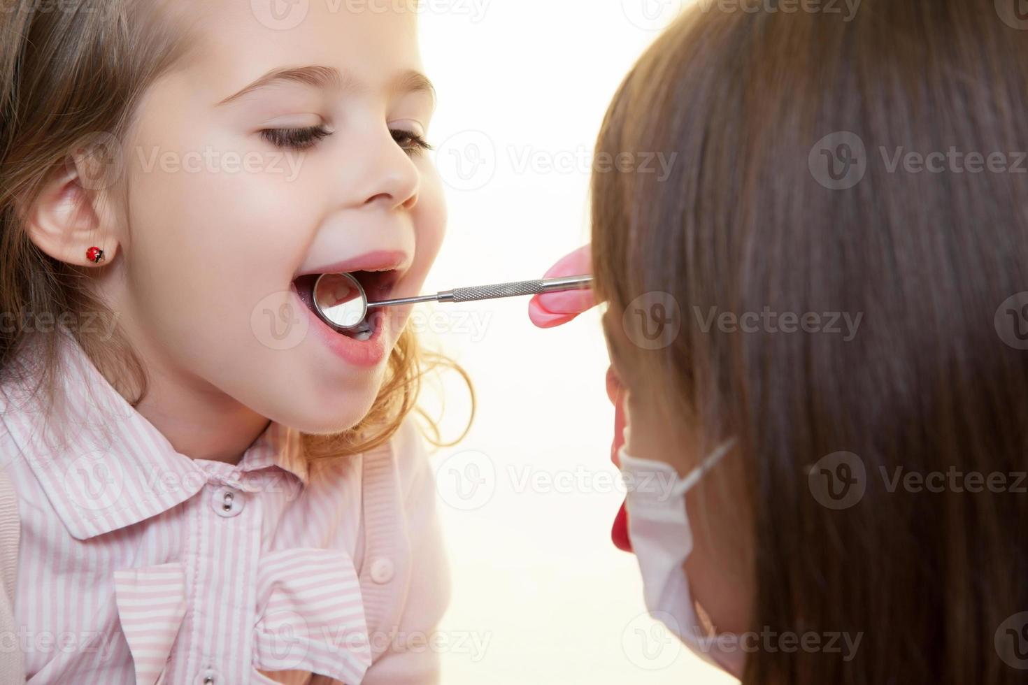 criança com dentista usando a ferramenta para olhar na boca foto