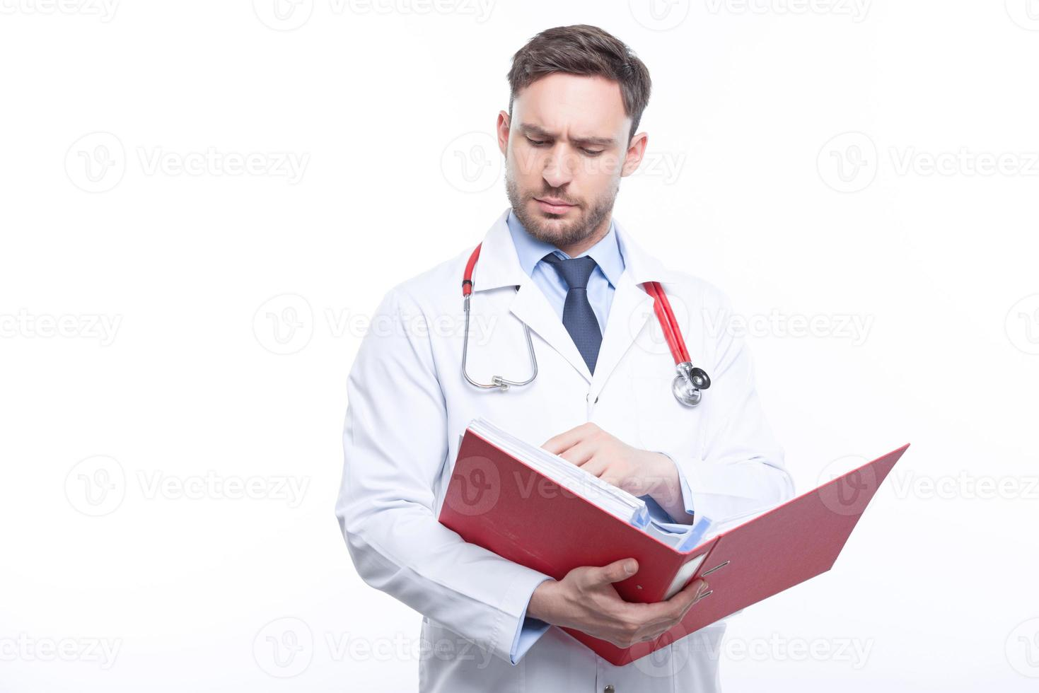 médico pensativo, segurando a pasta foto