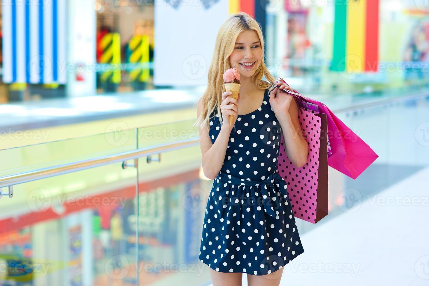menina adolescente com sorvete e sacolas de compras foto