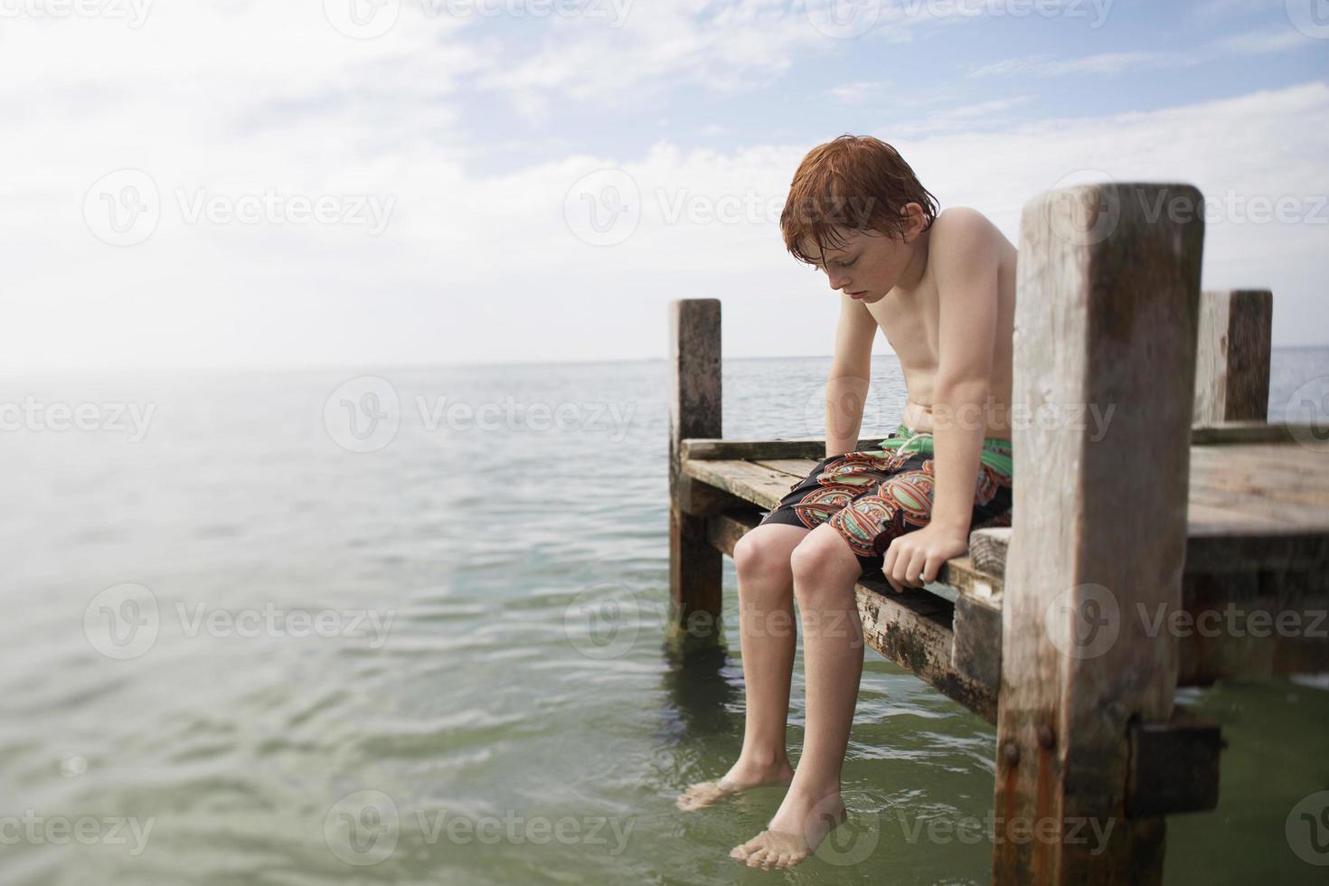 menino pré-adolescente sentado no final do cais foto