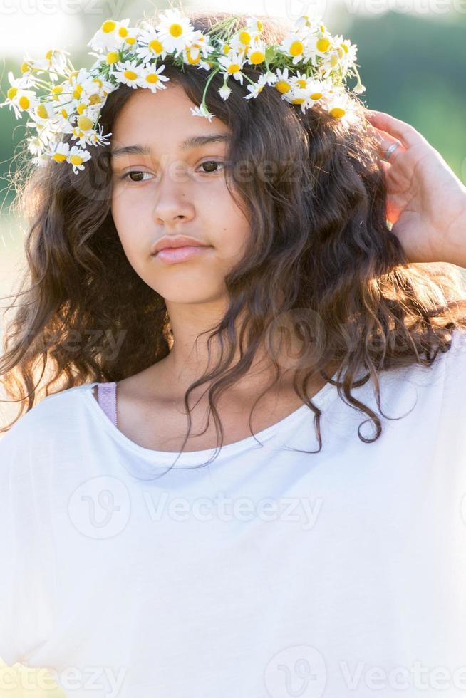 menina adolescente com uma coroa de margaridas no campo foto