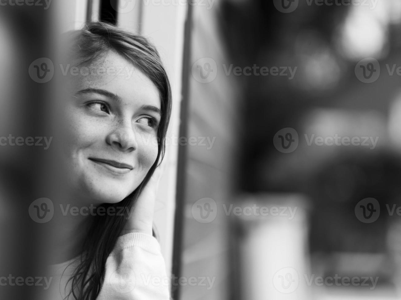 menina sorridente em pé na porta foto