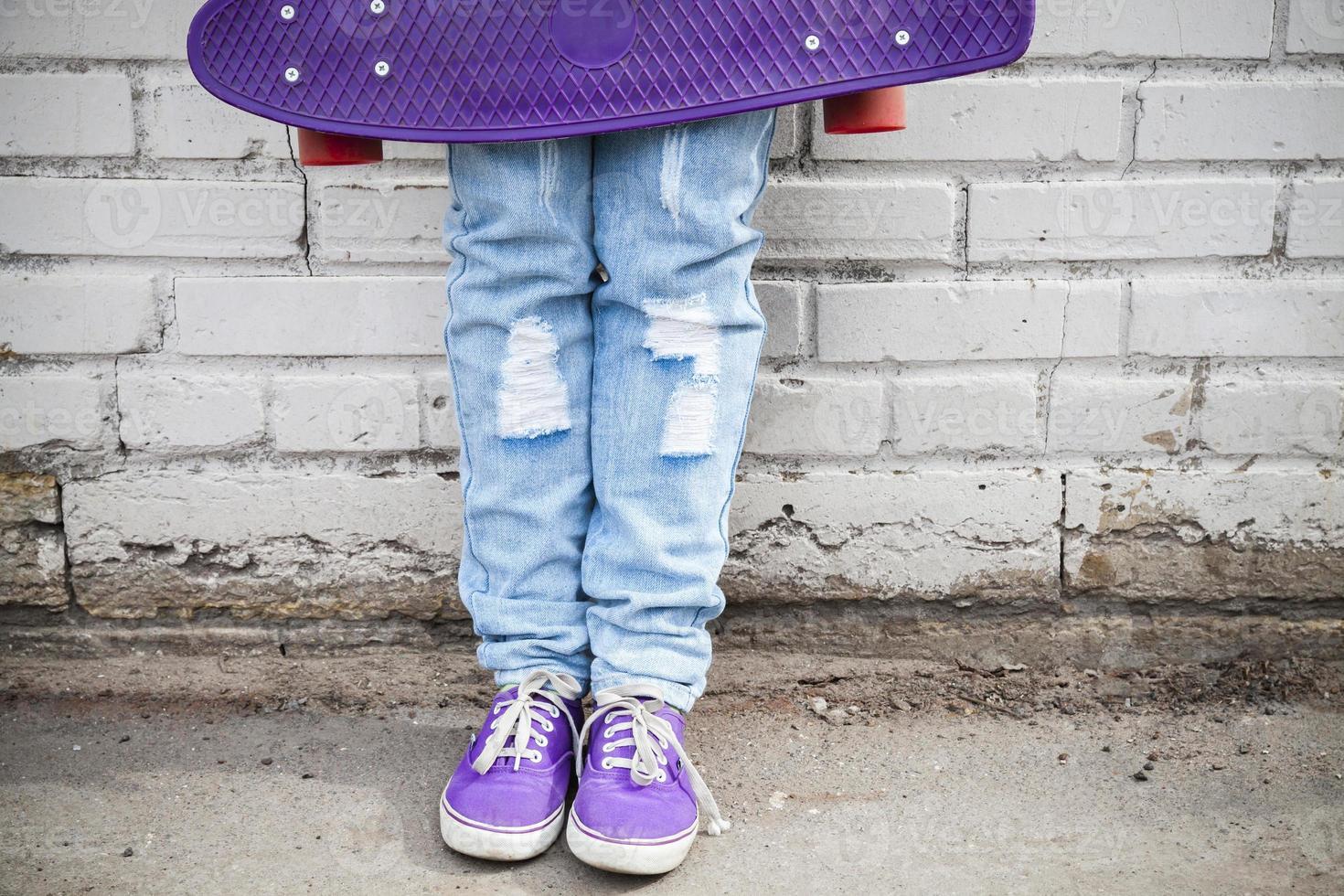 pés de adolescente em jeans azul com skate foto