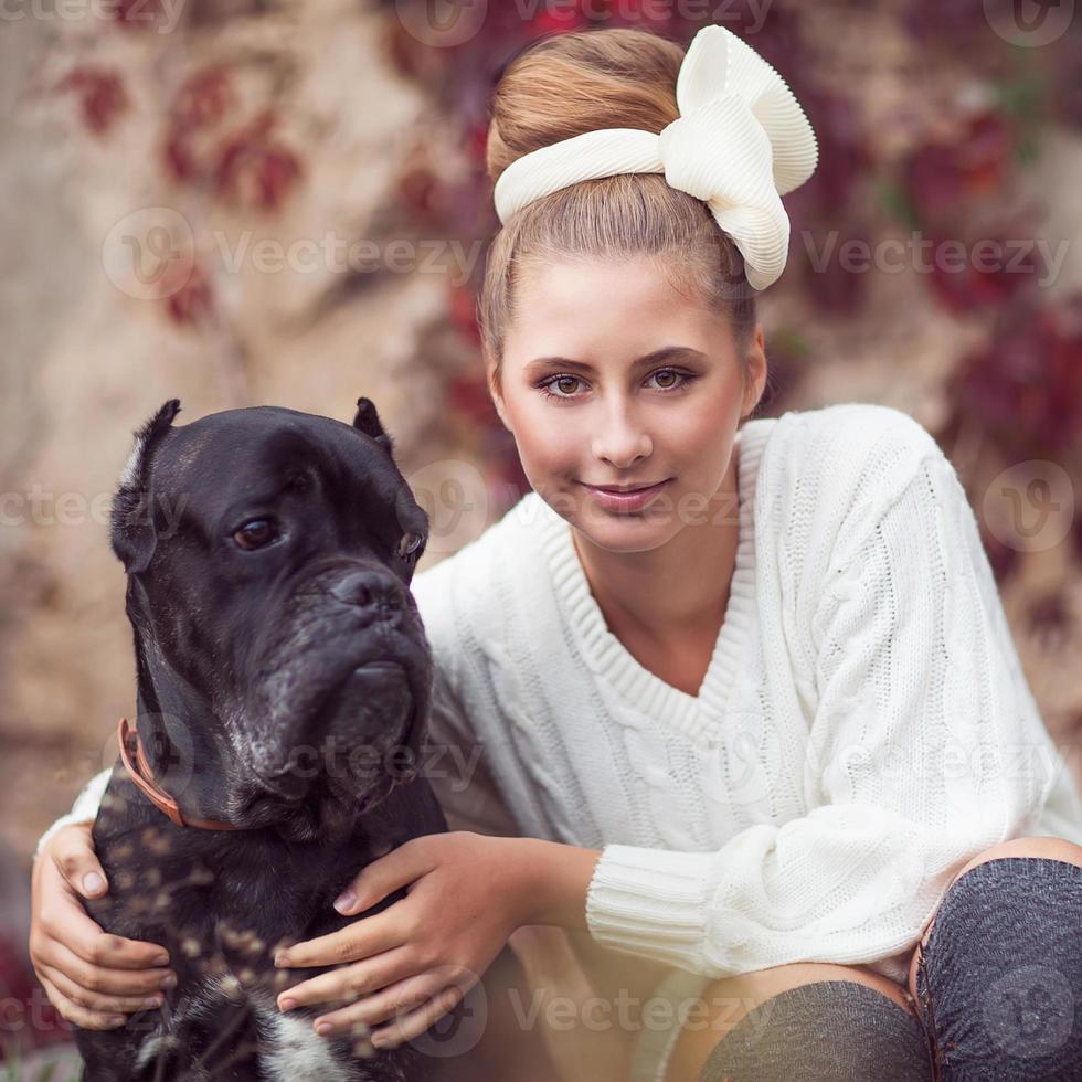 menina da moda com um cachorro rindo no parque outono foto