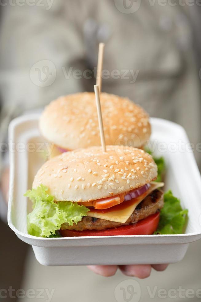 recipiente com hambúrgueres na mão masculina foto