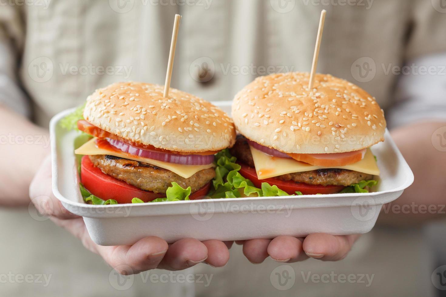 recipiente com hambúrgueres nas mãos masculinas foto