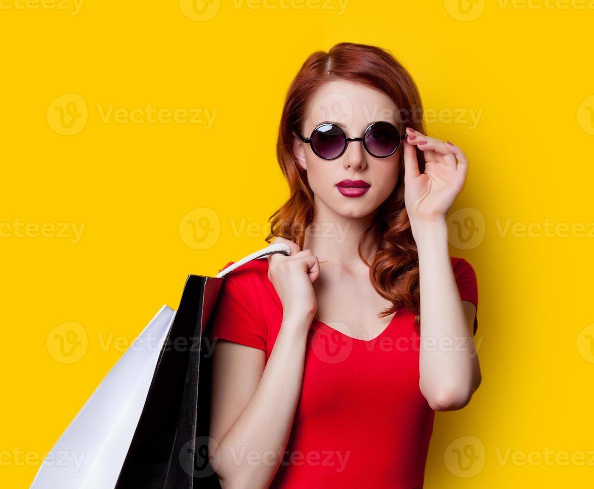 garota de vestido vermelho com sacolas de compras foto