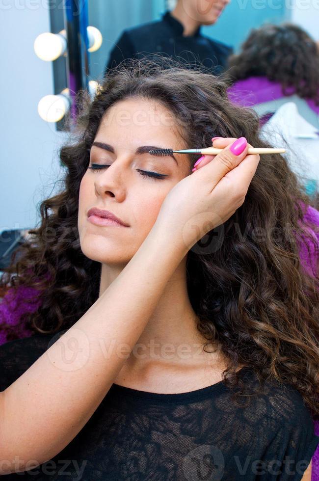 mulher colocando maquiagem rímel foto