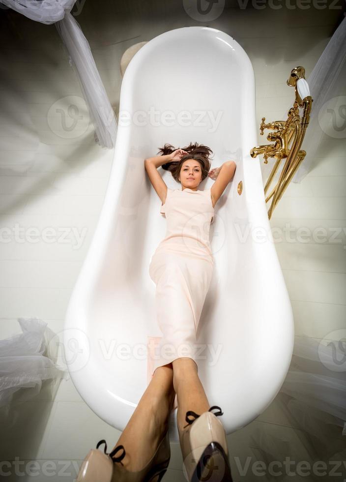 mulher de vestido longo, deitado no banho de luxo foto