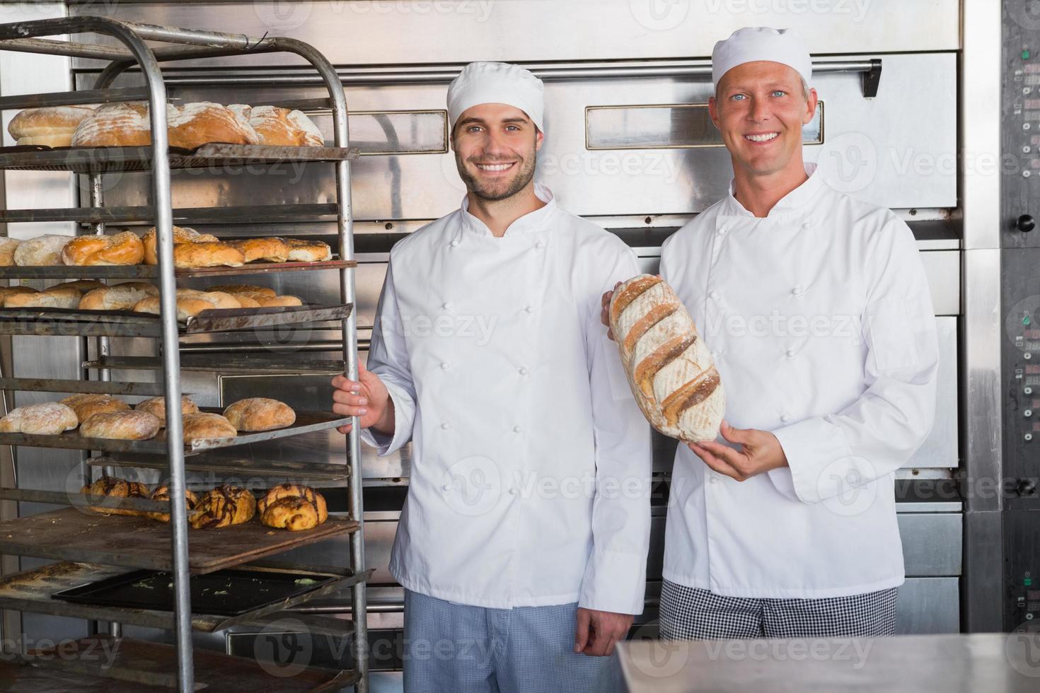 colegas sorridentes segurando pães frescos foto