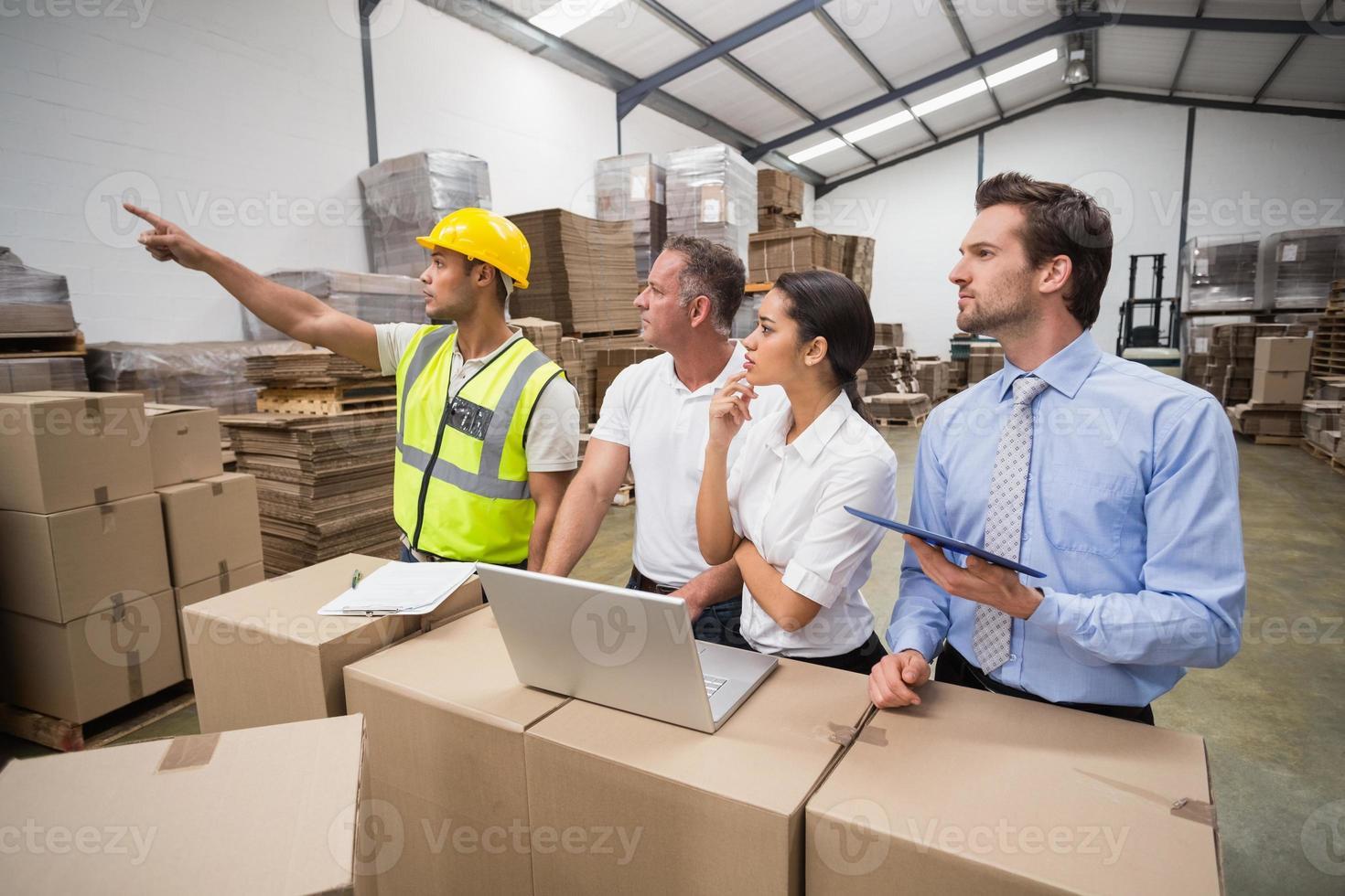 trabalhador de armazém apontando algo para seus colegas foto